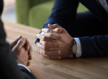 Clasped male hands of two businessmen negotiating at table